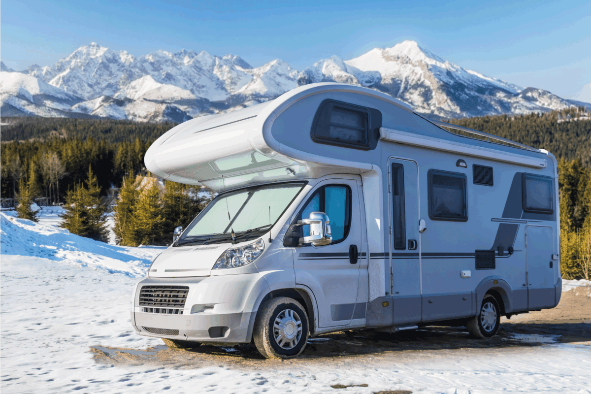 RV motorhome with background view of icy mountain peaks