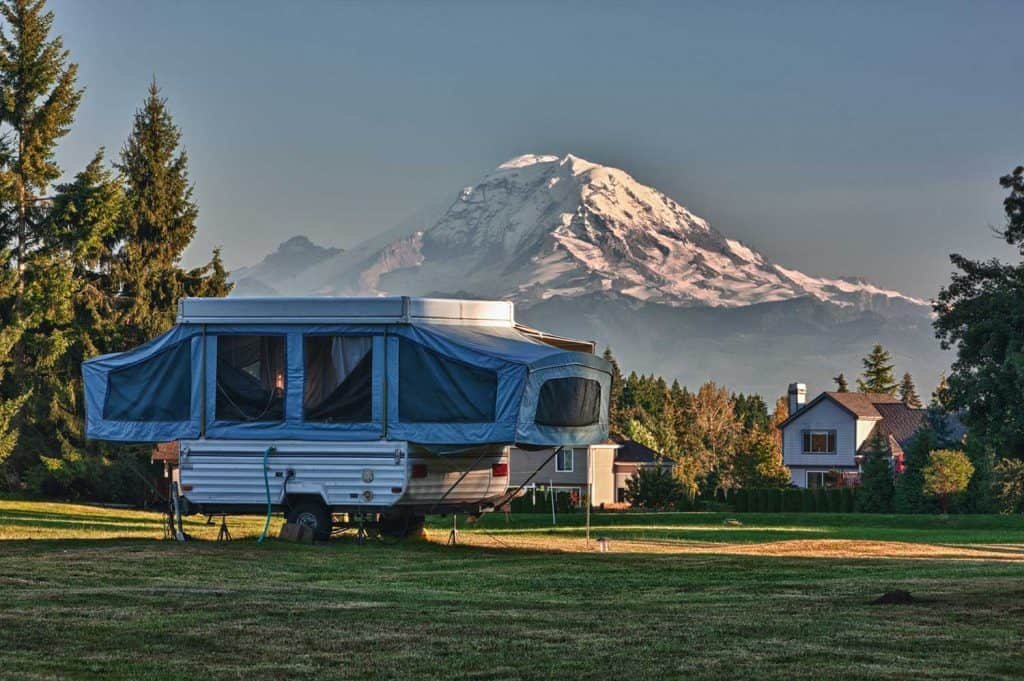 Tent camper in a neighborhood back yard with mountain in the background