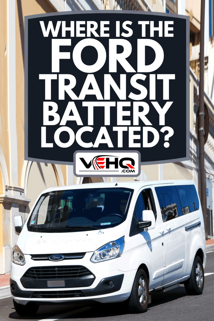 A white passenger bus Ford Transit in the city street, Where Is The Ford Transit Battery Located?