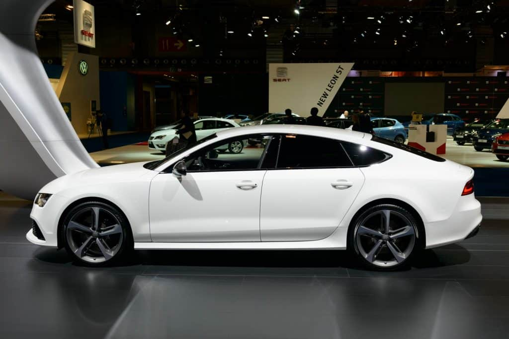 White Audi RS7 Sportback four door executive car on display at the Brussels motor show. People in the background are looking at the cars.