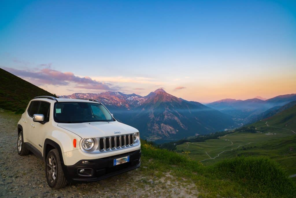 White Jeep Renegade parked on dirt road at panoramic view point on the Italian Alps from above. Colorful sky at sunset, mist on the valley below