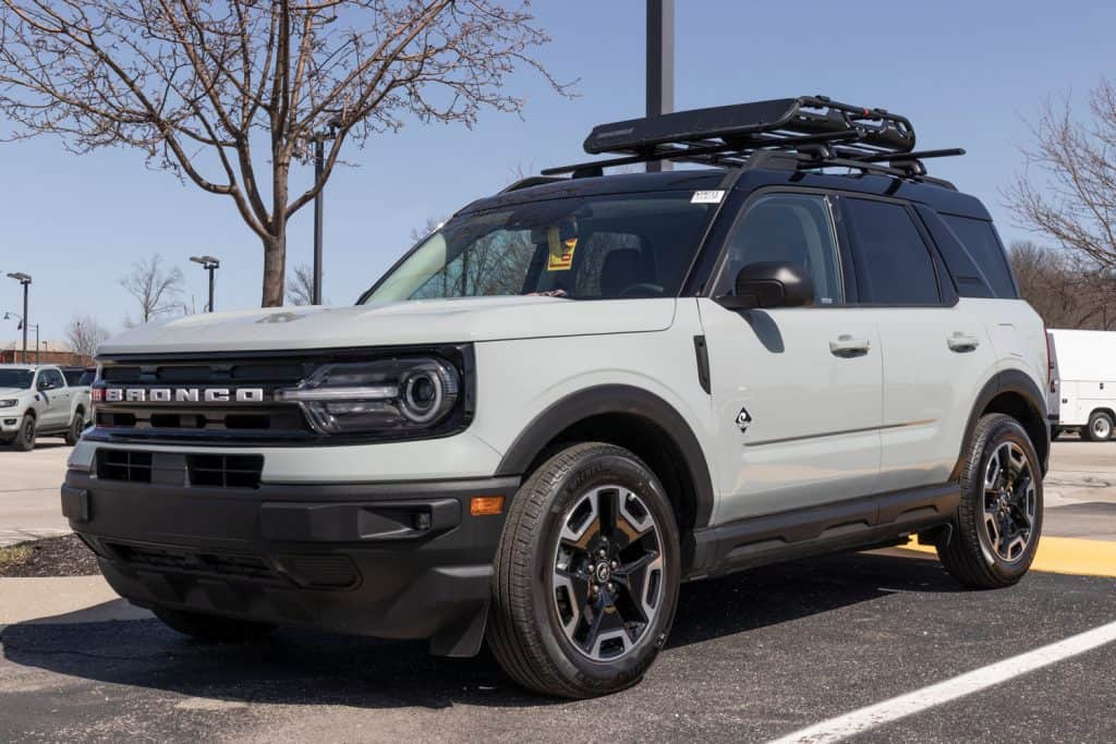 White brand new Ford Bronco with a carrier on top photographed on the parking lot