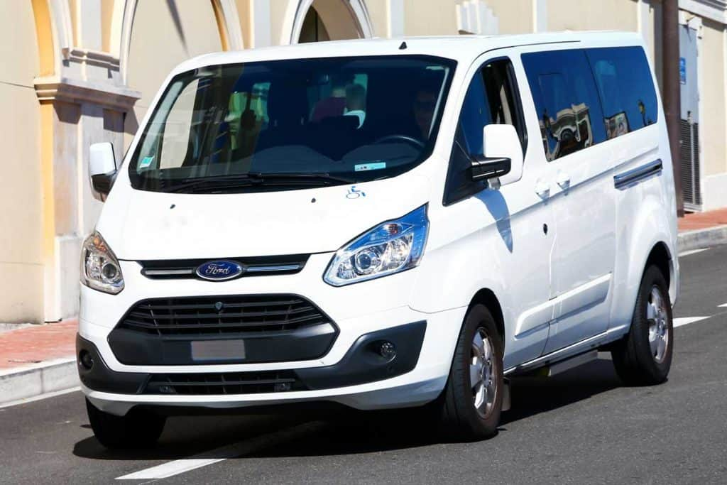 White passenger bus Ford Transit in the city street, Where Is The Ford Transit Battery Located?