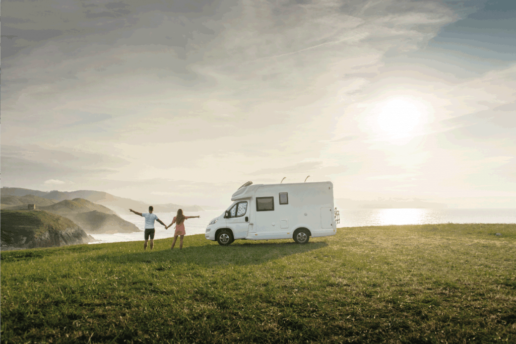 Young couple traveling with their motor home standing by the sea with arms raised. How Big Is My RV's Grey Water Tank