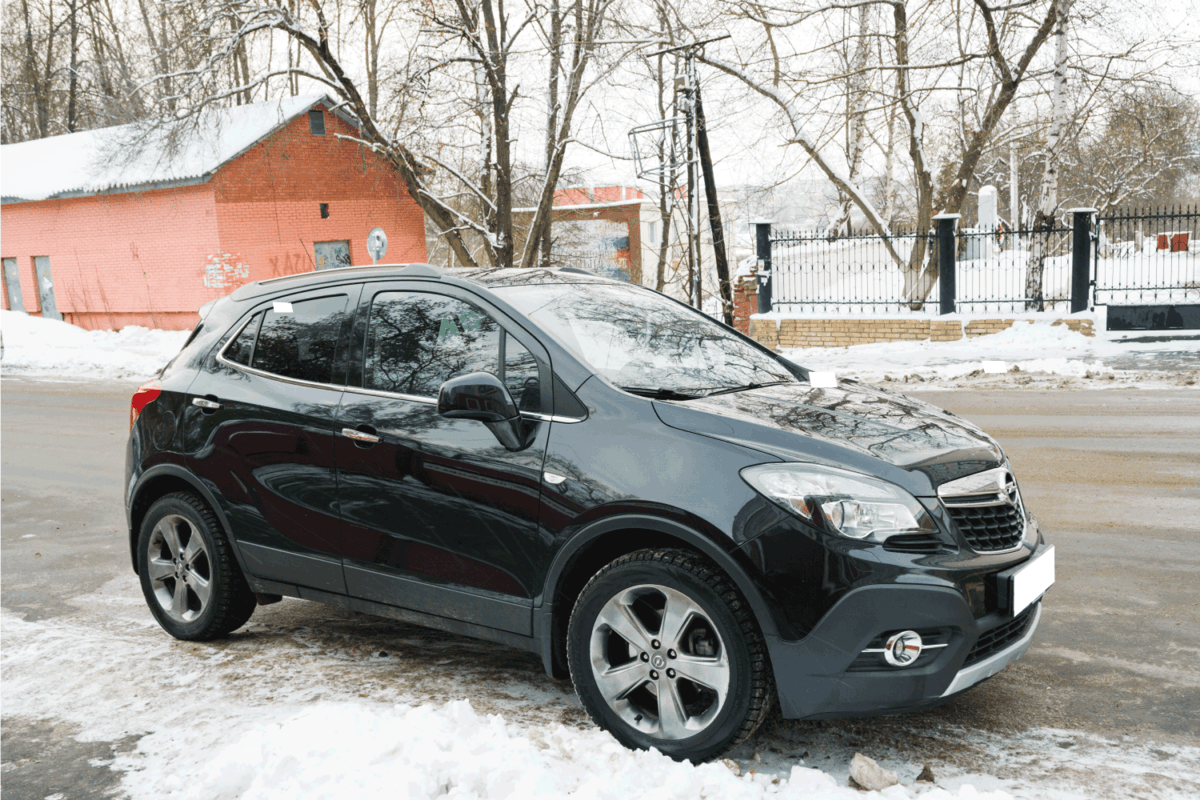 crossover SUV vehicle parked on the street with snowfall