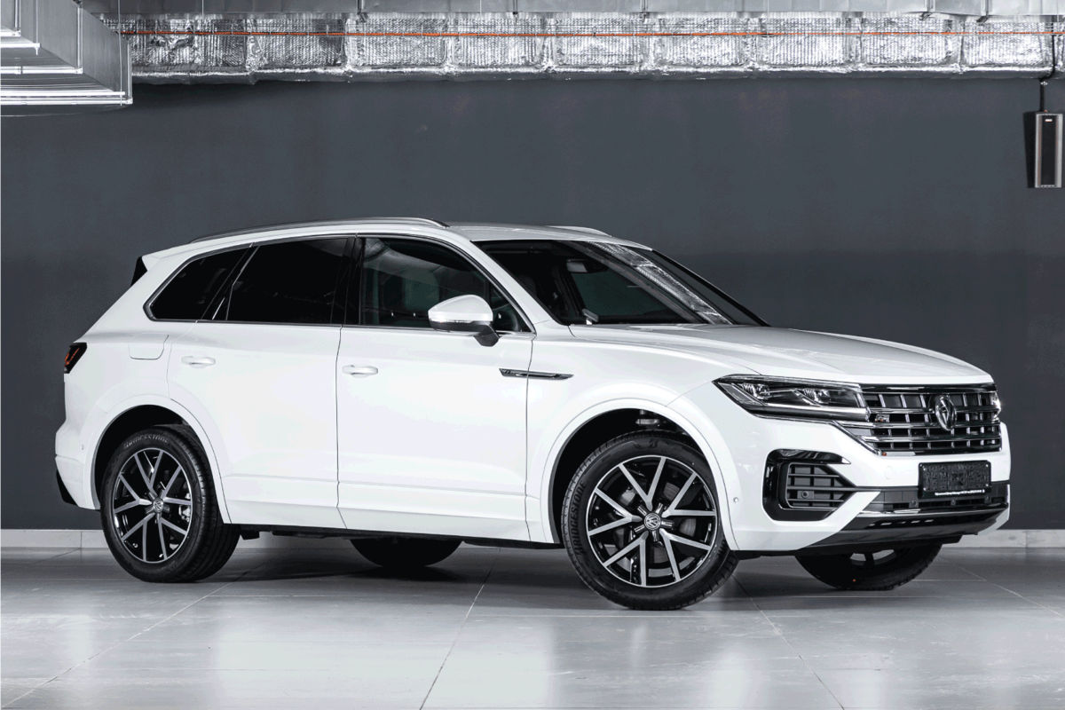 white Volkswagen Touareg, expensive crossover car parked on black background