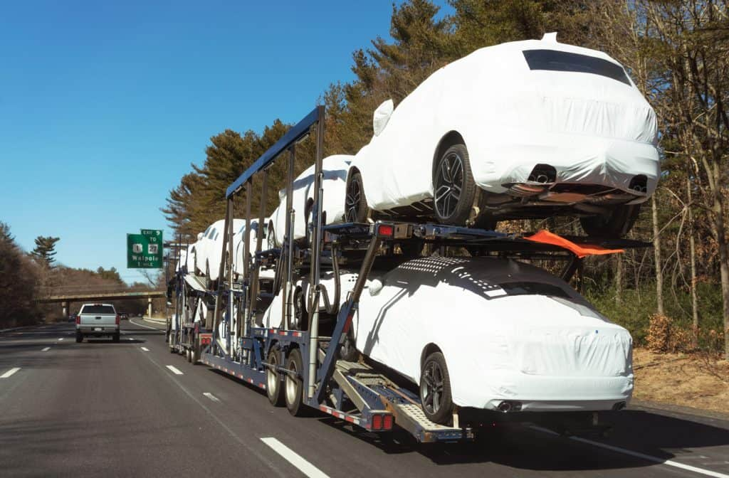 A car transporter truck delivering brand new cars on a US freeway.