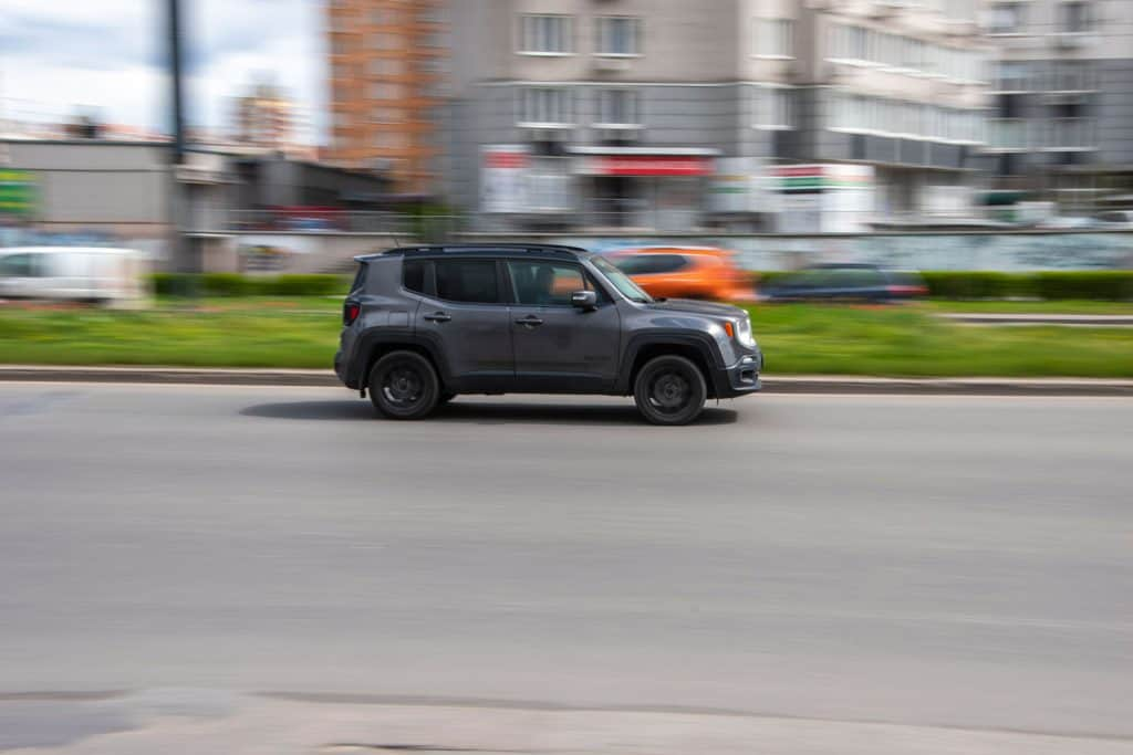 A gray Jeep renegade moving fast on the street