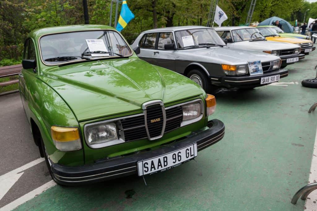 A green Saab 97 GL displayed at an outdoor car show