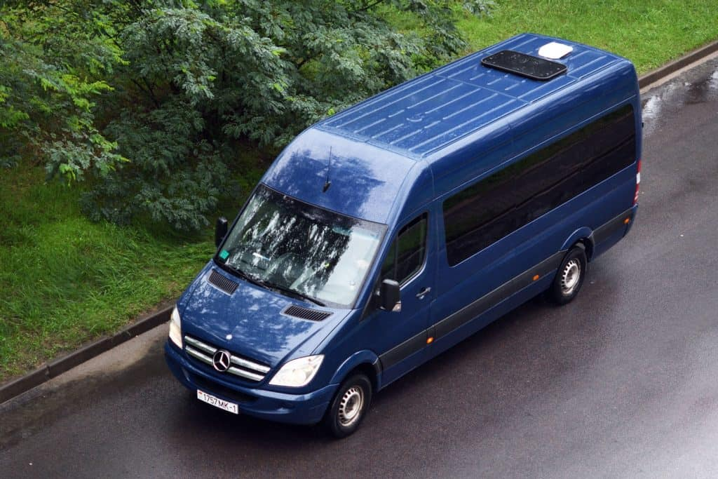 A huge blue colored Mercedes Benz Metris moving on the highway