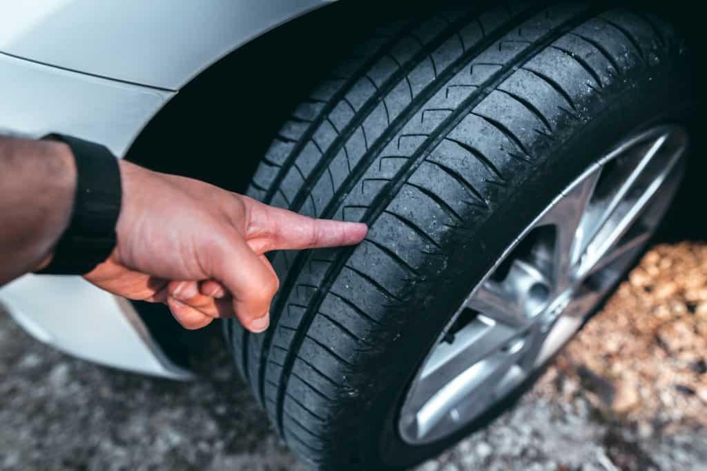 A human hand checking a tire tread