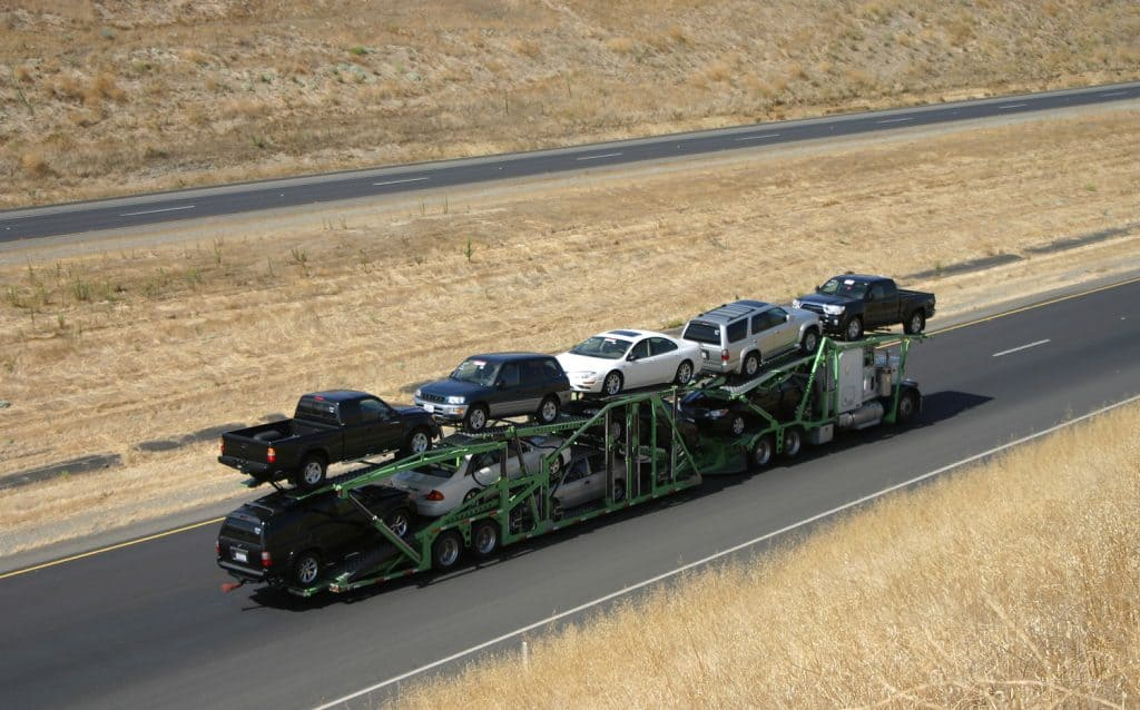 A large truck delivers new cars via highway.