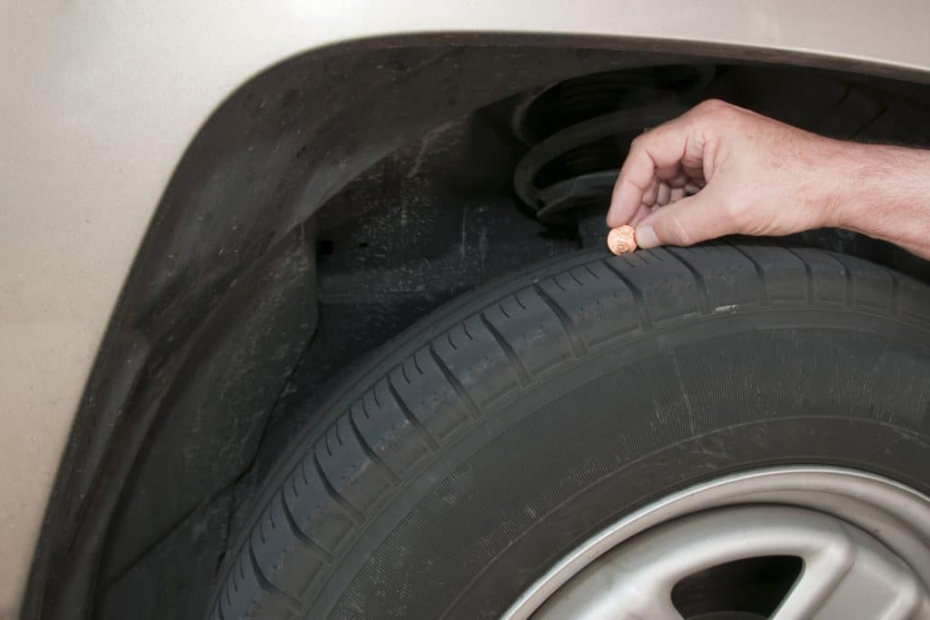 A man inserting a coin in the tire tread