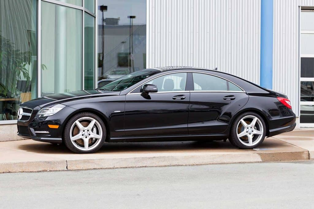 A new Mercedes CLS550 on display in front of a car dealership showroom