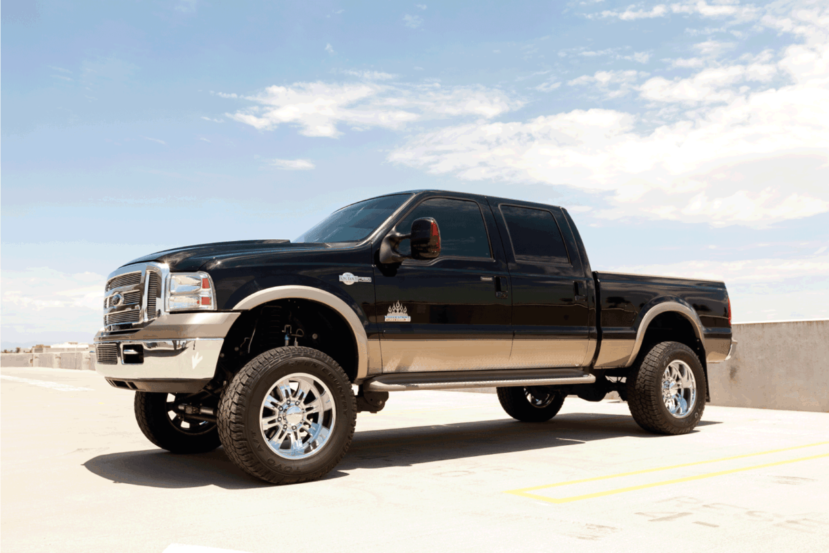 A parked Ford F250 truck with a lift kit, custom wheels and a diesel engine, king ranch edition