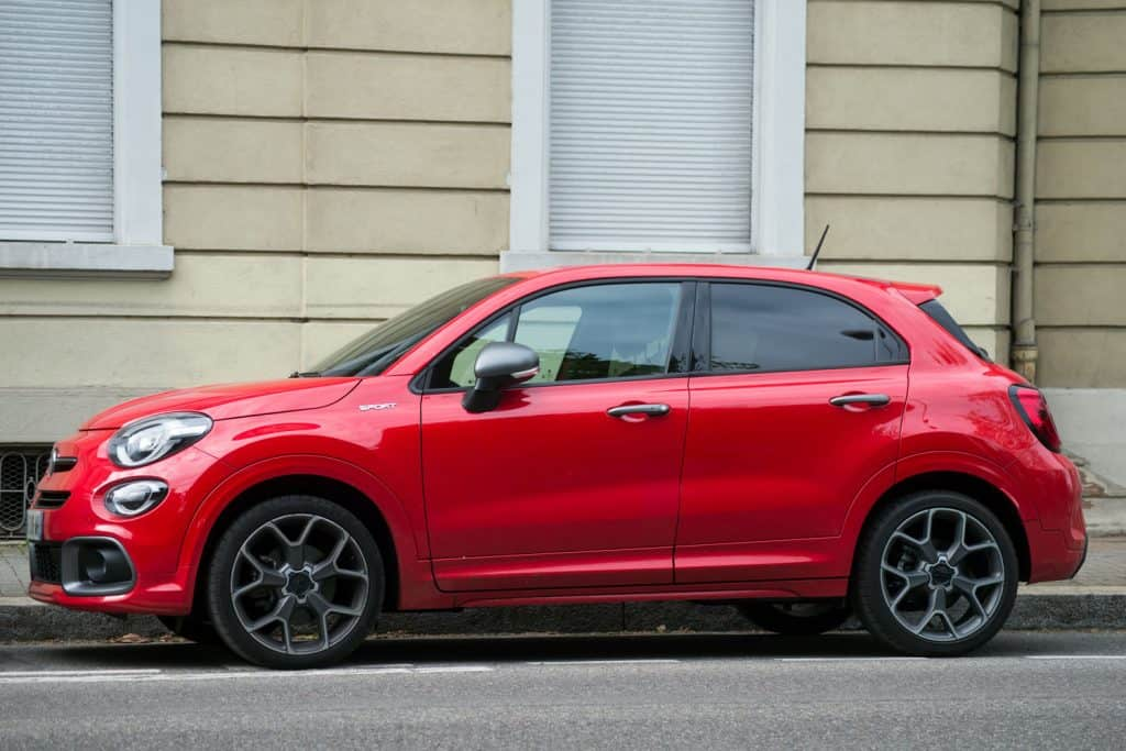 A red Fiat 500L parked on the side of the road