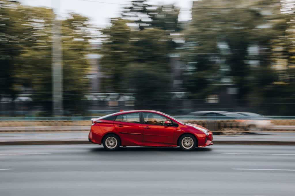 A red Toyota Prius moving fast on the highway