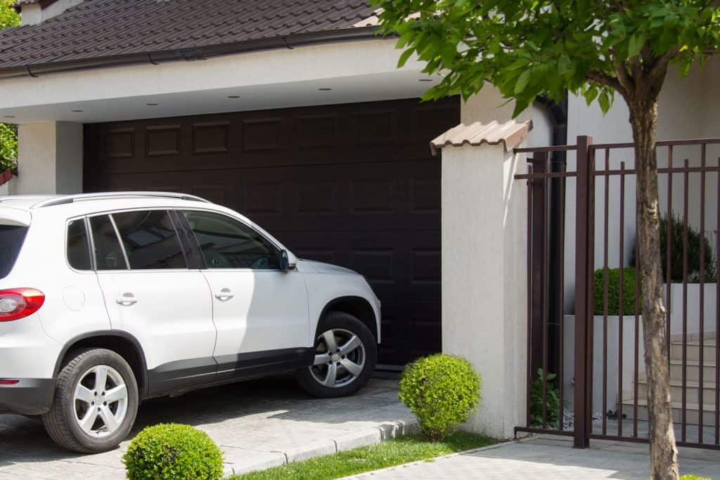 A white mid-sized SUV headed inside the garage