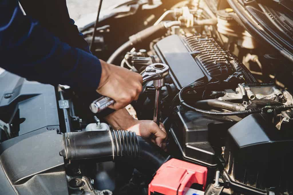 Auto mechanic hands using wrench to repair a car engine
