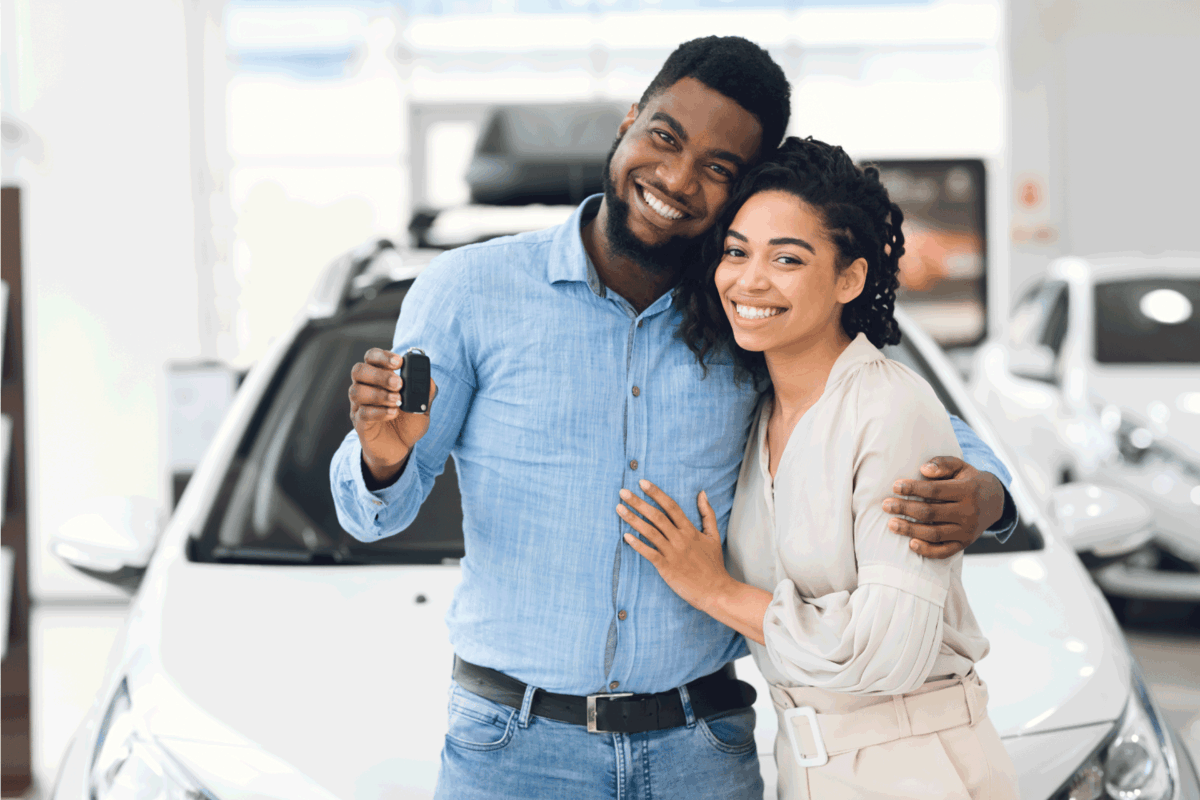 Car Buyers. couple Showing New Vehicle Key To Camera Smiling And Hugging Near Auto In Dealership Showroom.