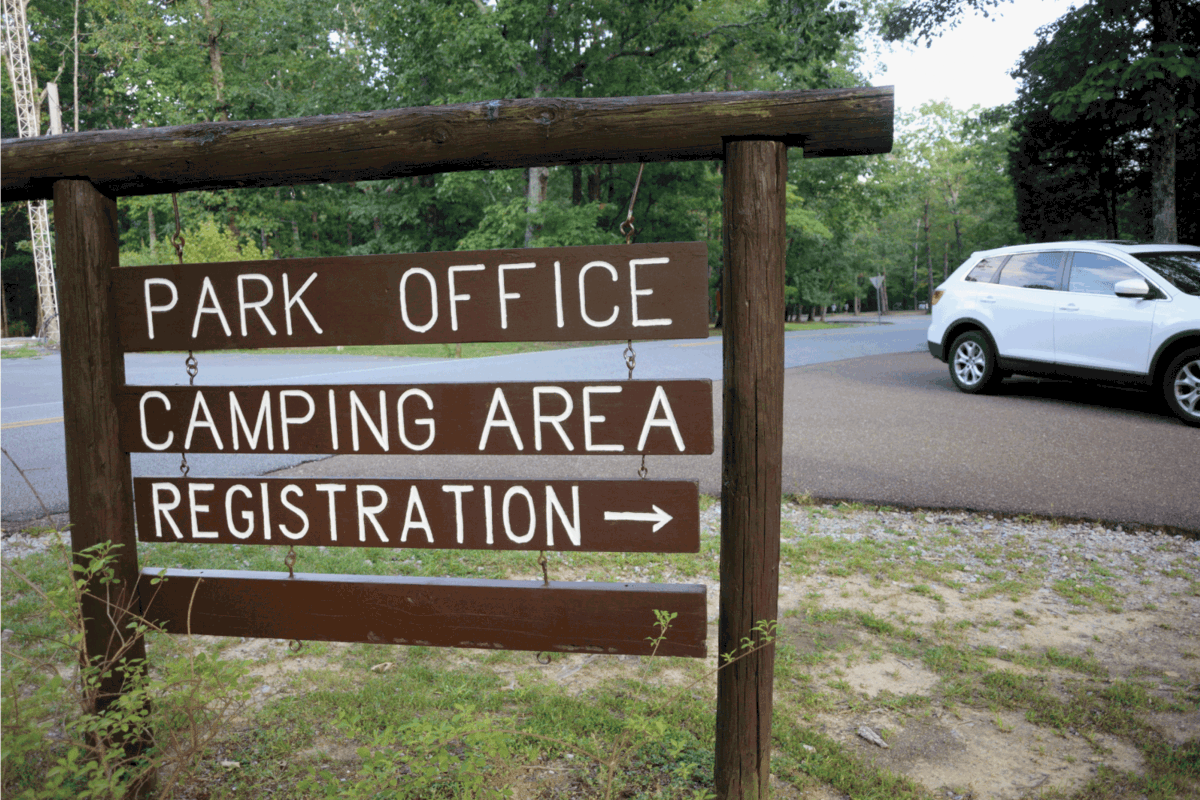 Close up of park office camping area registration road arrow sign with passing car in public state park.