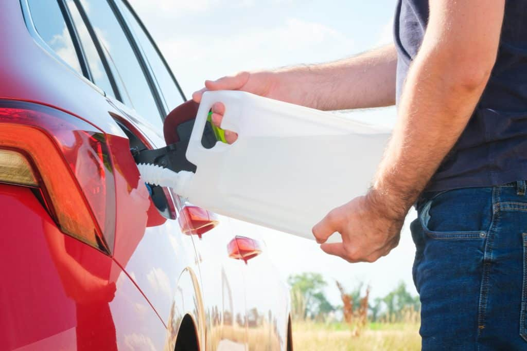 Close up woman refilling the red car with fuel or a diesel engine fluid from canister in the field