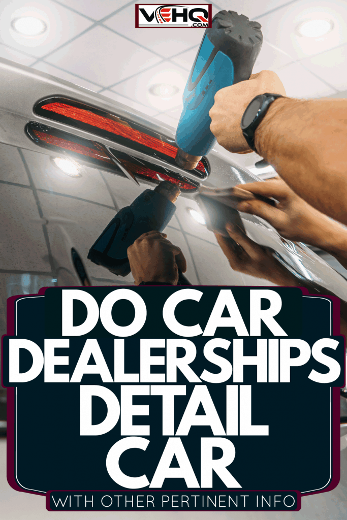 A worker doing some detailing work on the back windshield of the car, Do Car Dealerships Detail Cars? [With Other Pertinent Info!]