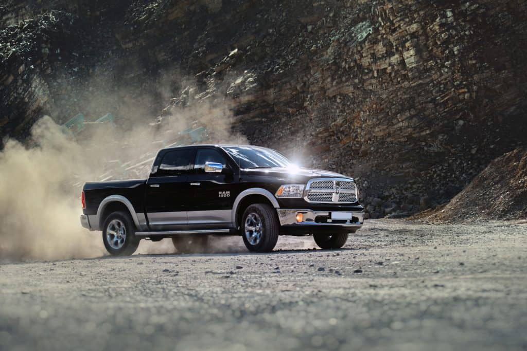 Dodge RAM 1500 with dust swirling from the quarry in which it is driving