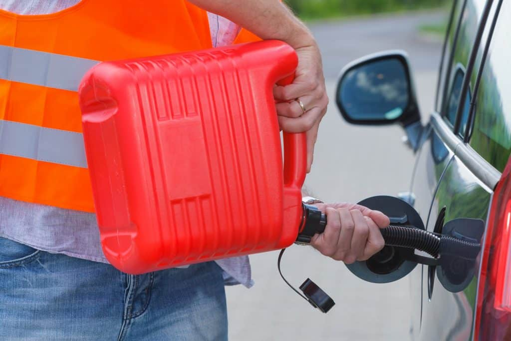 Driver fills the fuel in an empty car tank from red canister on the side of the road