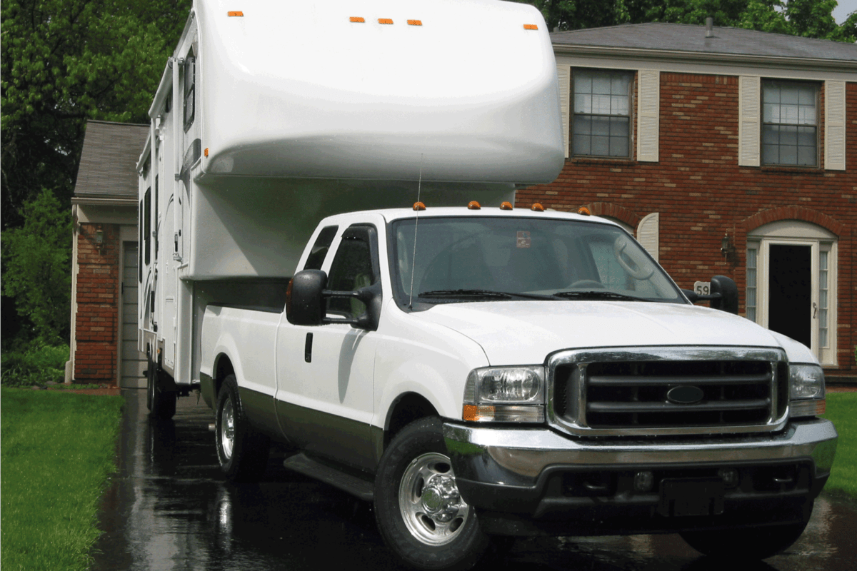Ford f350 with Titanium 5th wheel, both are in white. parked on a walkway