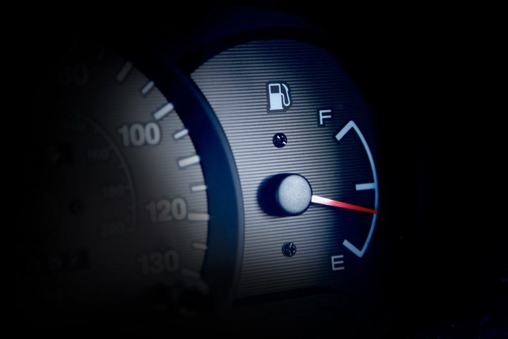 Fuel gauge in a car starting to point towards empty.