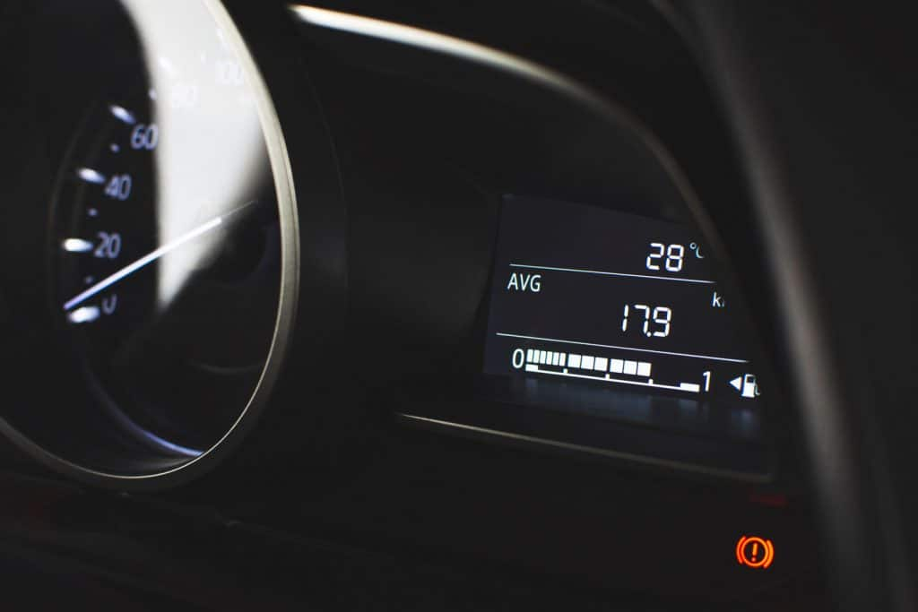 Fuel meter digital gauge and fuel average mileage range meter and handbrake warning light in luxury car.