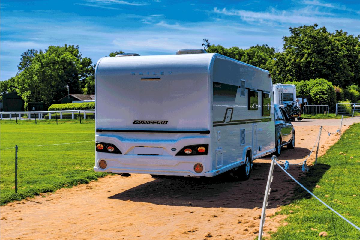 Hot sunny day in summer. A car is towing a trailer Caravan onto a caravan site