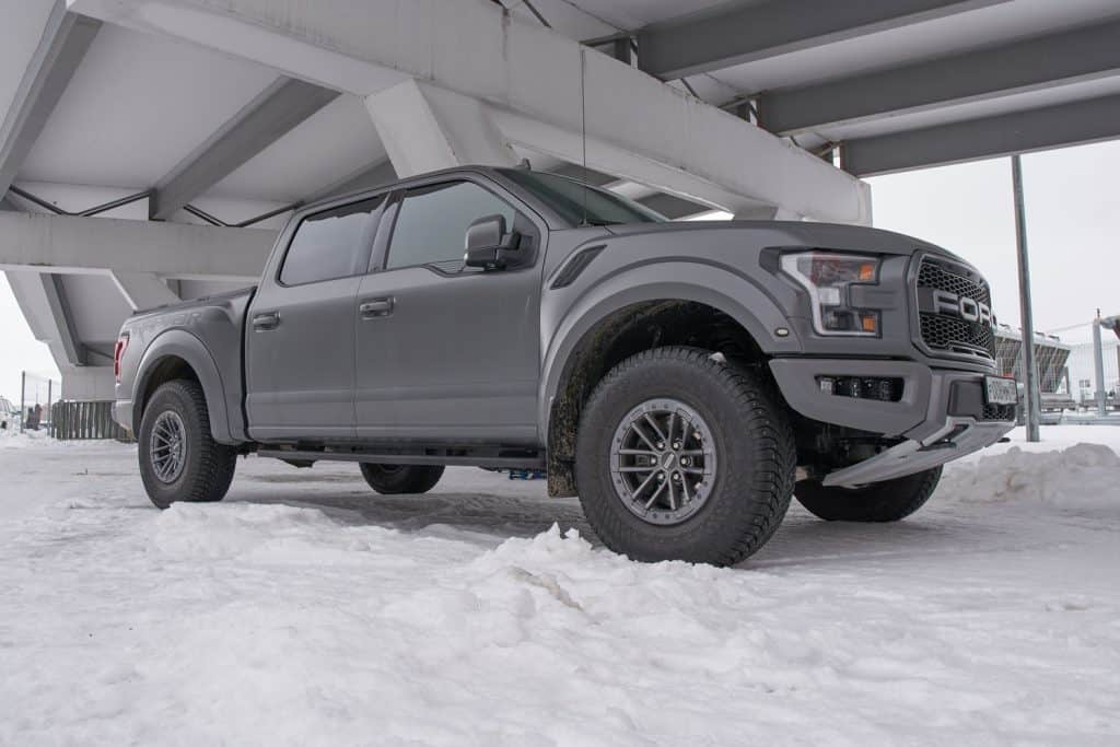 Huge dark grey colored Ford F150 photographed under the bridge