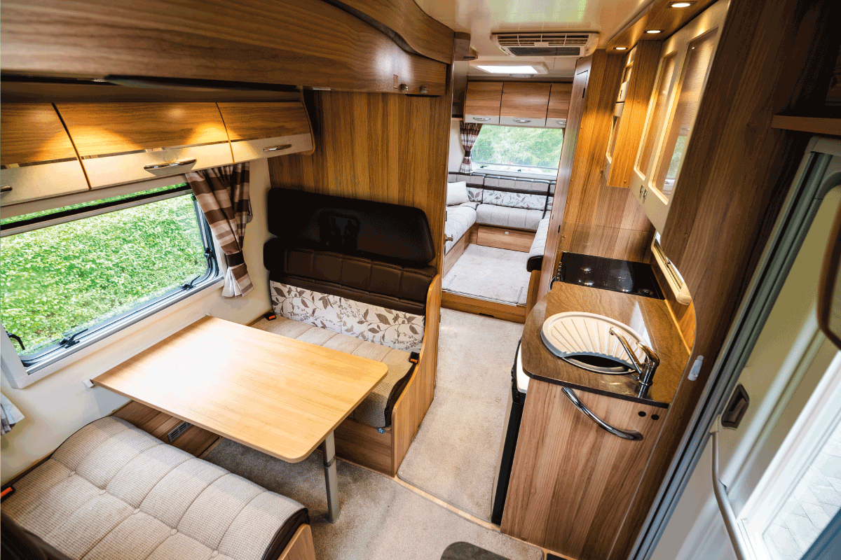 Luxury large open plan motor home interior with seating area and table for several occupants. Large window letting in a lot of daylight. interior with no people. RV USB Outlets Not Working - What To Do