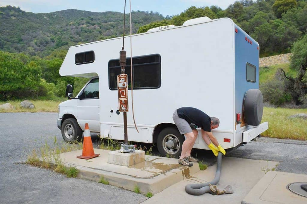 Man serving recreational vehicle in dumping station