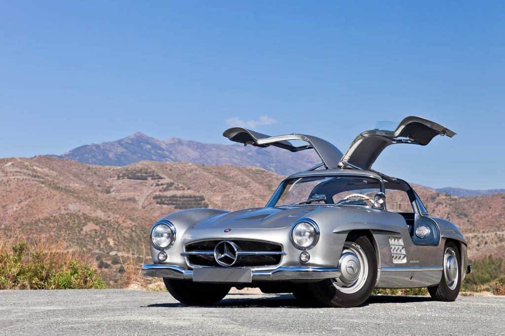 Mercedes 300 SL Gullwing parked on a cliff by the road in the mountains