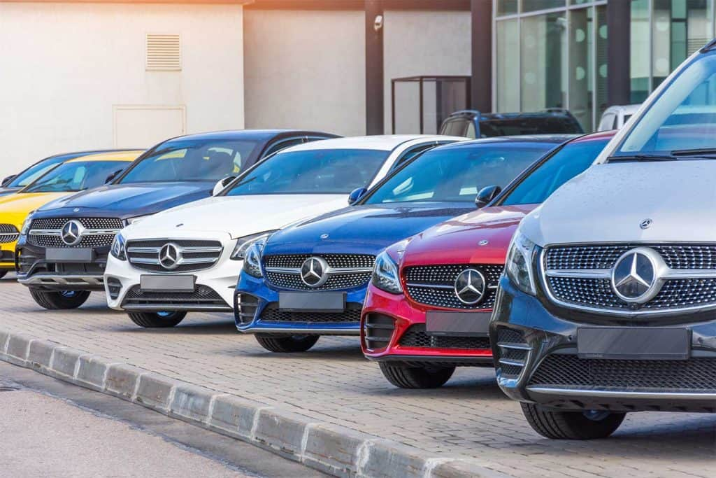 Mercedes-Benz different class and color in a row in front of a dealership