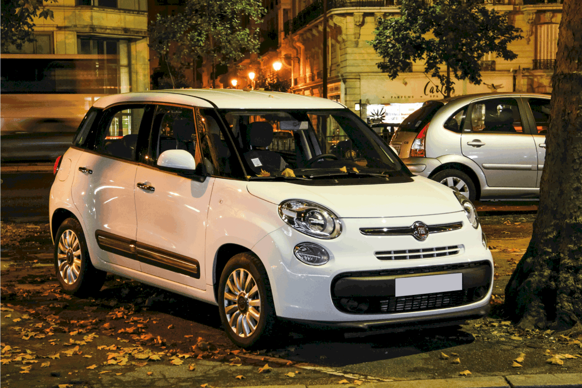 Motor car Fiat 500L is parked in the city street.