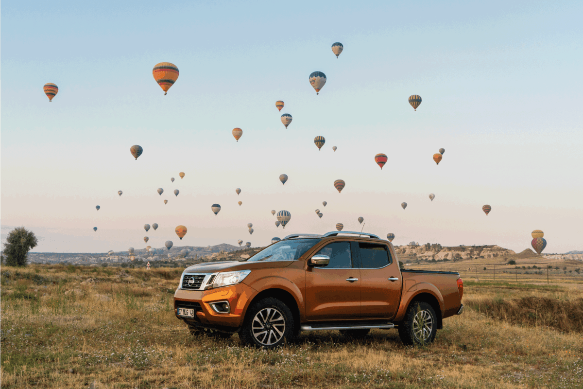 Nissan NP300 Navara stopped on the hill, hot air ballons on the background