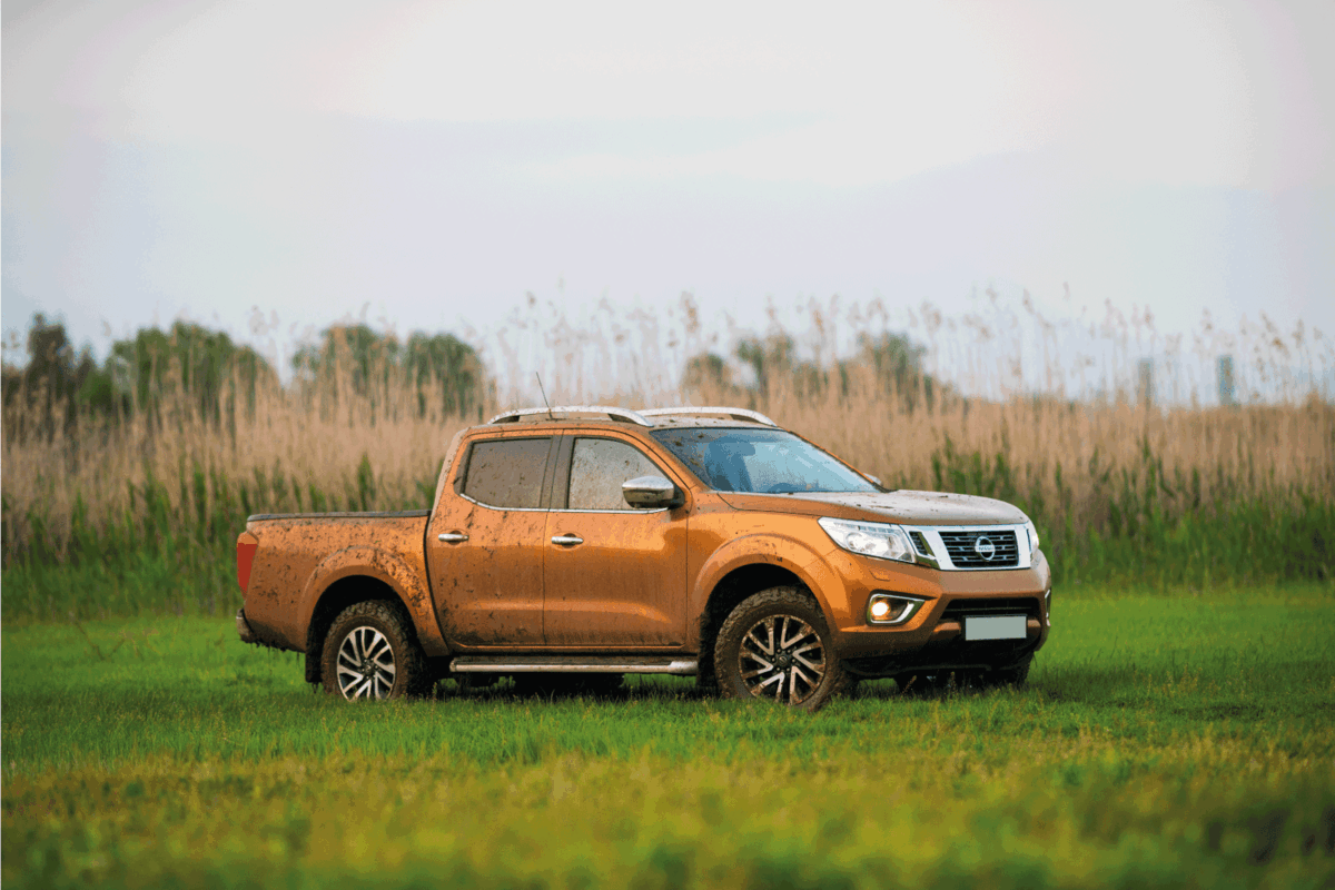 Pickup Truck (Nissan NP300 Navara ) parked at lawn, covered with mud after passing the pond.