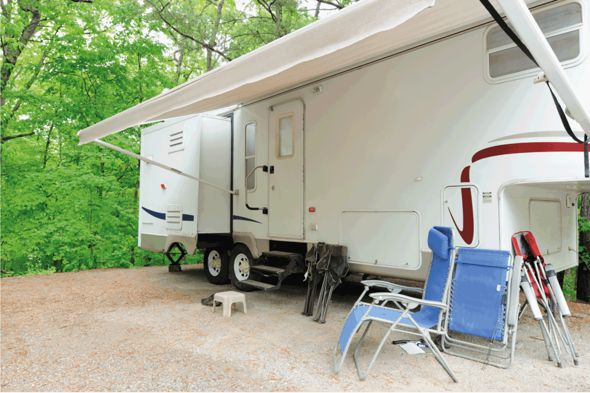 Recreational vehicle fifth wheel travel trailer in wooded campsite with awning, electric steps, and folding chairs.