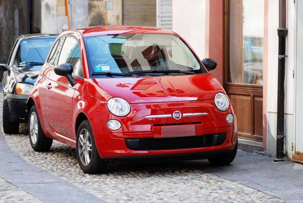 Red Fiat 500 parked in the street