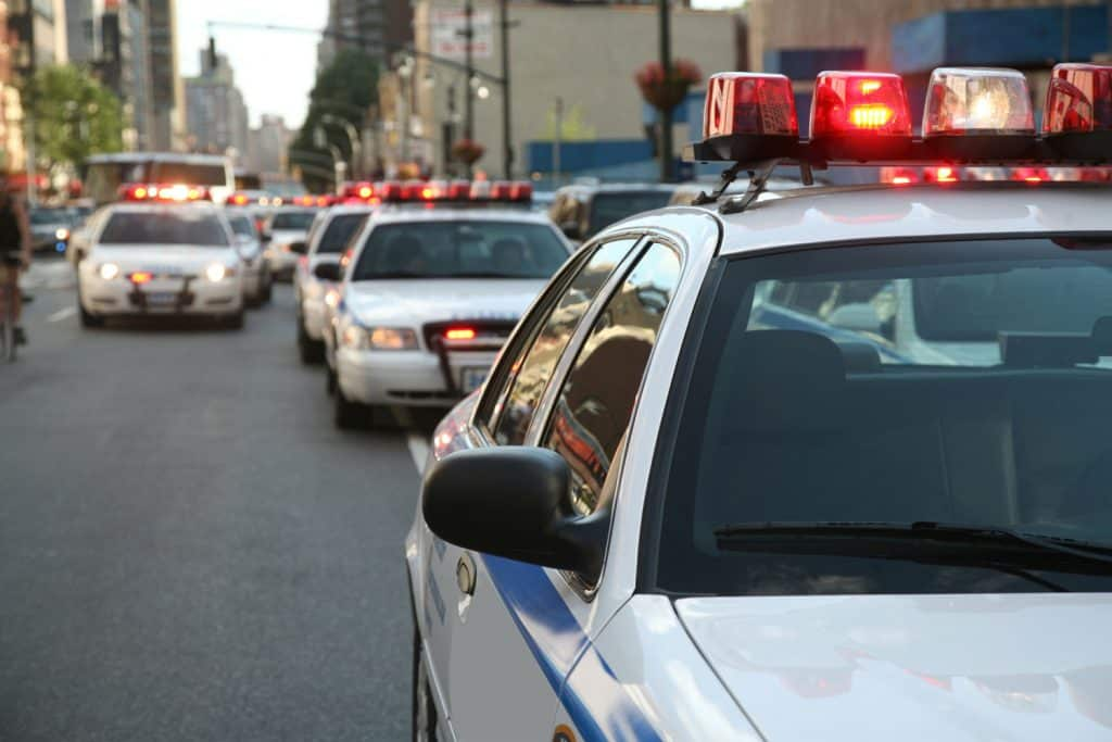 Row of police cars with flashing lights and sirens on the streets
