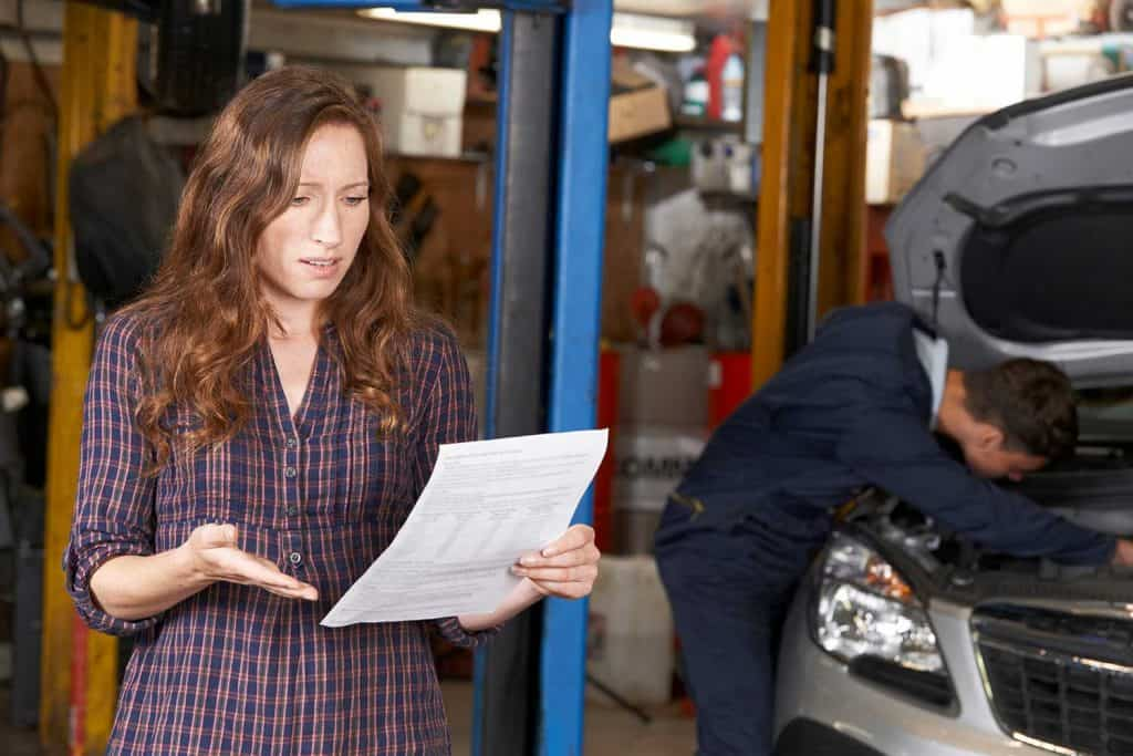 Shocked female customer looking at garage bill