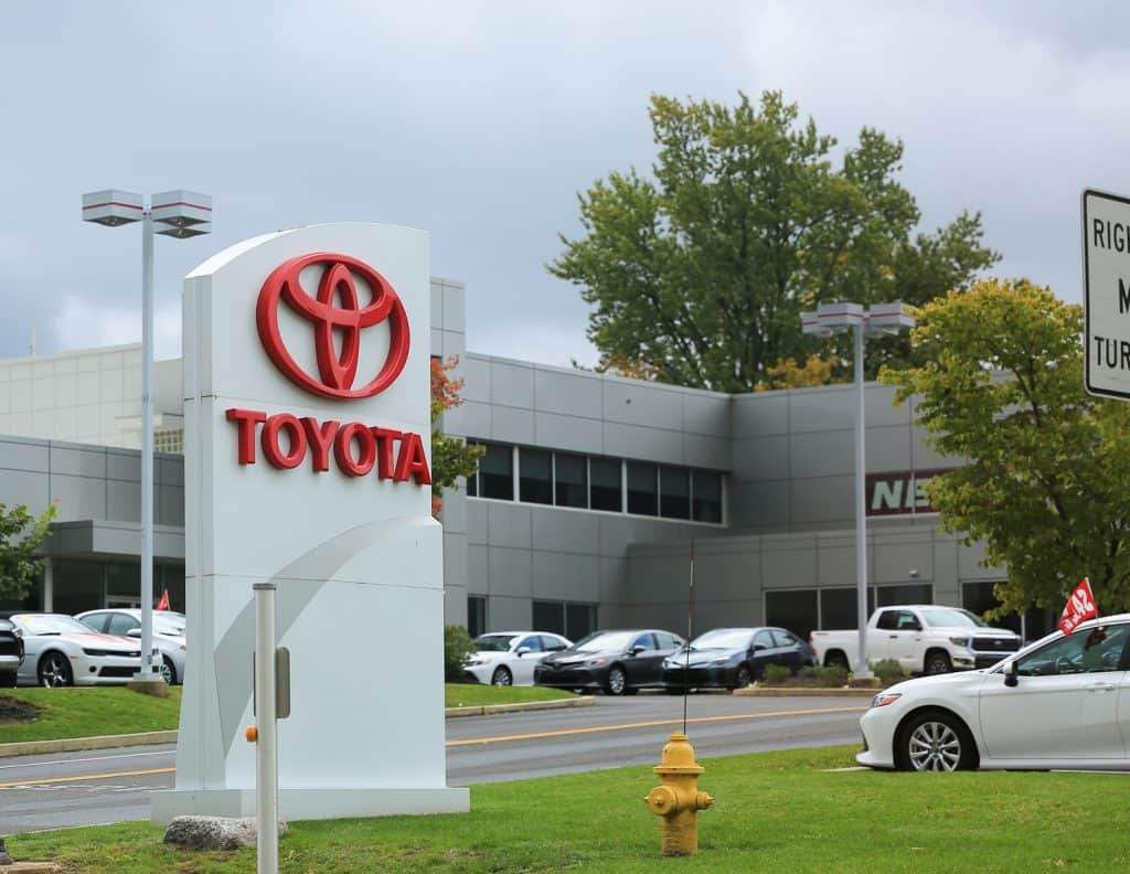 Toyota dealership sign against blue sky. Toyota is the world's market leader in sales of hybrid electric vehicles.