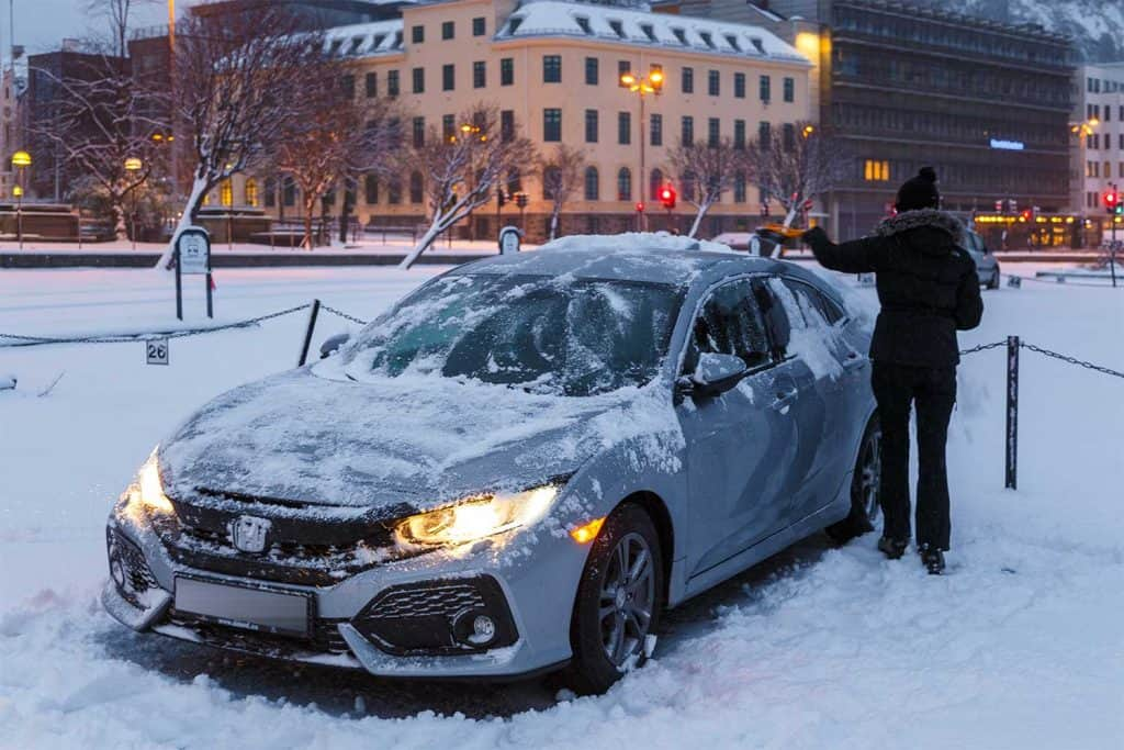 Woman cleaning her Honda Civic from the snow