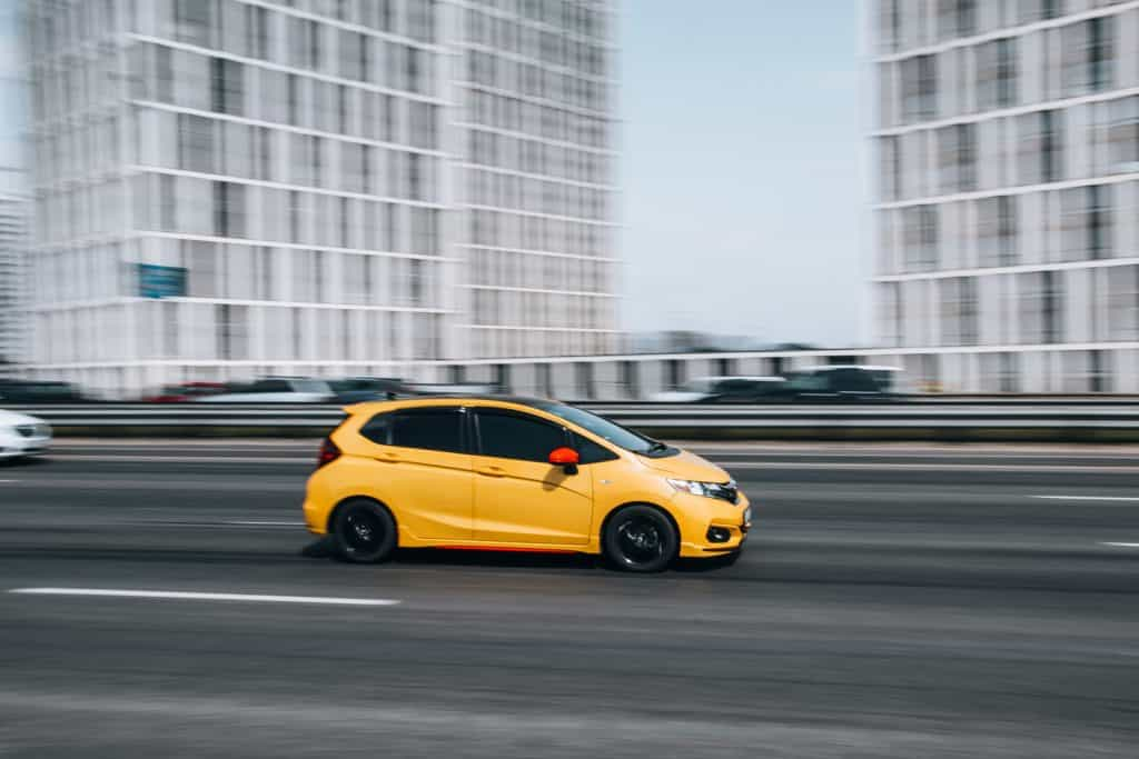 Yellow Honda Fit car moving on the street.