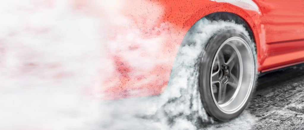 car burns rubber off its tires in preparation