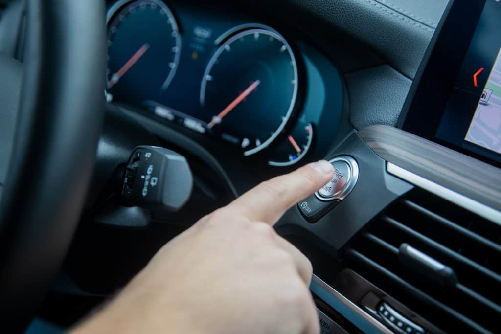 male finger presses the start stop engine button on a car dashboard. close-up, soft focus, in the background the dashboard and car speedometer in blur, side view